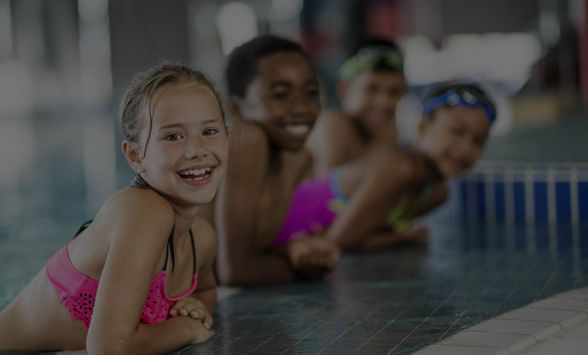 a group of kids leaning on the side of a pool, covered under FitSecure's insurance policies