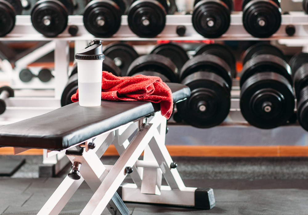 A workout bench, towel, water bottle and weights all covered under our fitness insurance